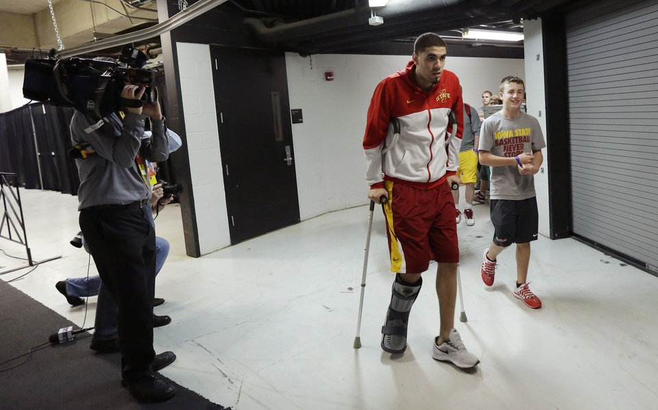 Photo - Iowa State's Georges Niang, center, arrives in uniform for practice for the NCAA men's college basketball tournament, Saturday, March 22, 2014, in San Antonio. Niang broke his foot during a game Friday night and will not play when Iowa State faces North Carolina on Sunday. (AP Photo/Eric Gay)