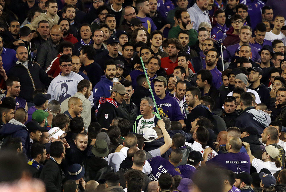 Photo - Fiorentina's fans scuffle during the Italian Cup final match between Fiorentina and Napoli in Rome's Olympic stadium Saturday, May 3, 2014. At least one fan and one police officer were reportedly shot before the Italian Cup final between Napoli and Fiorentina, and the fan was in serious condition. As a result, the start of the final was delayed, and there were scenes of violence inside the stadium with a firefighter injured by fireworks thrown from the stands. The shootings occurred in an area where Napoli fans were gathering for the match, the ANSA news agency reported. (AP Photo/Gregorio Borgia)