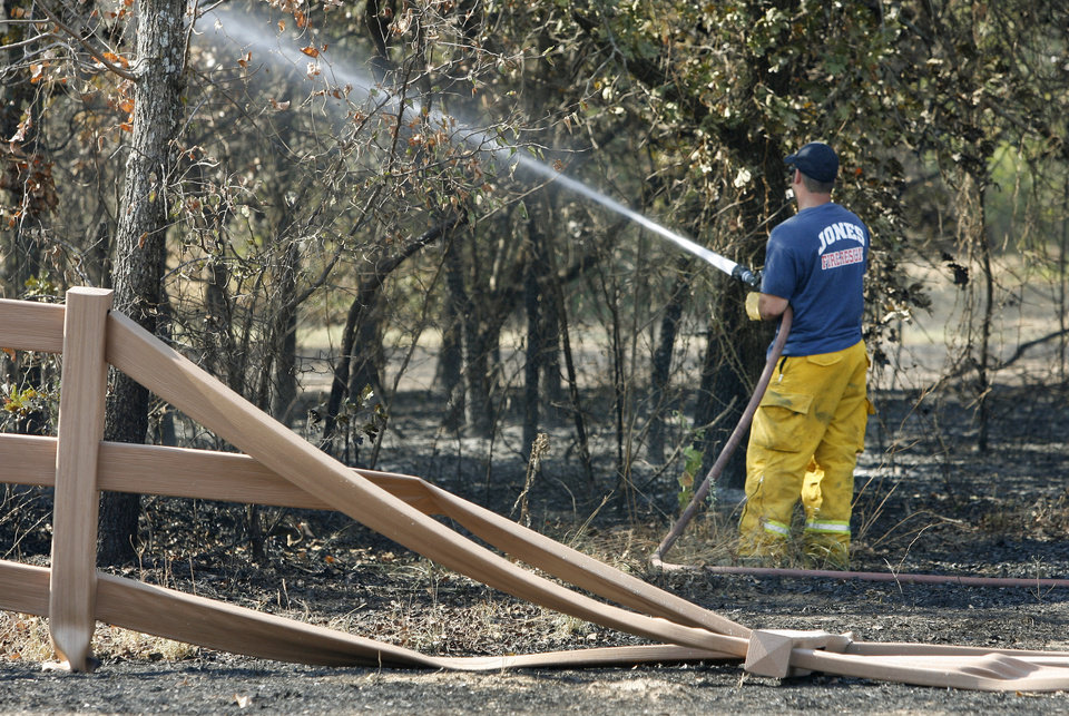 Photo - A Jones firefighter sprays hot spots near Britton road and Prosper drive after wildfires swept through the area in Oklahoma City , Wednesday, August 31, 2011. Photo by Steve Gooch, The Oklahoman