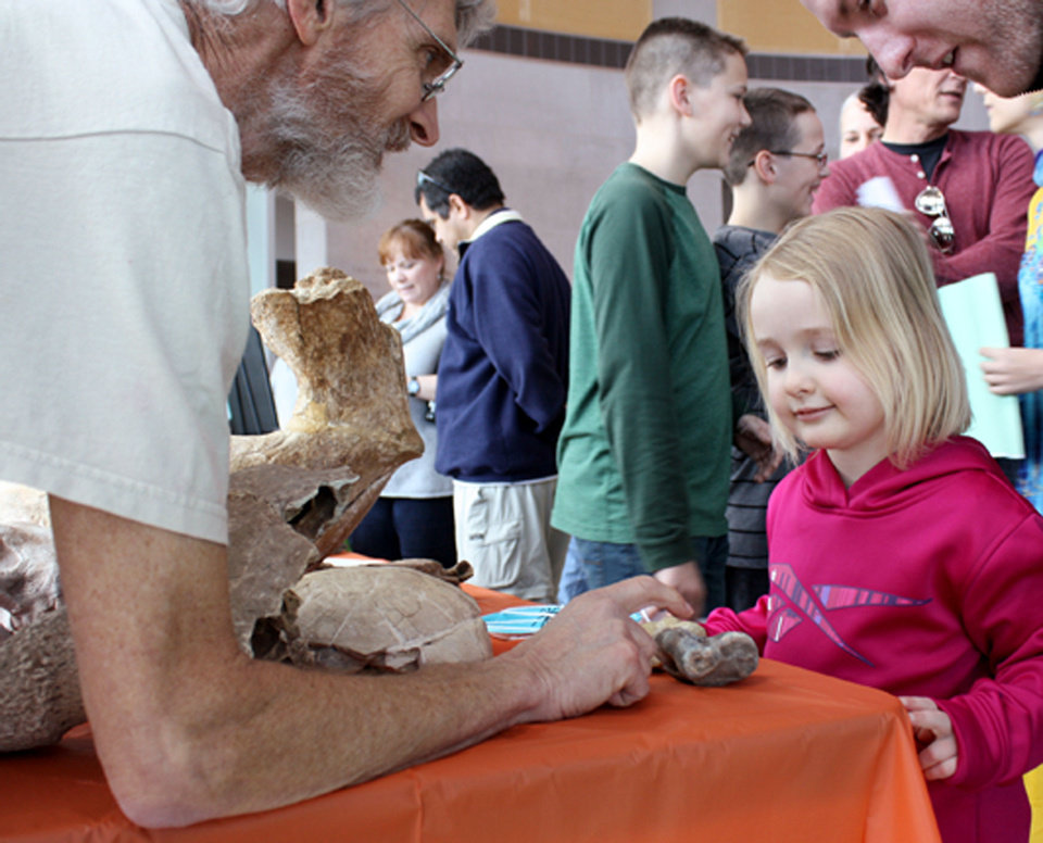 Nick Czaplewski, associate staff curator, shows  Elizabeth Sanders, 4, some old bones.