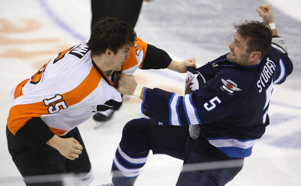 Photo - Philadelphia Flyers' Tye McGinn (15) fights with Winnipeg Jets' Mark Stuart (5)  during the second period of an NHL hockey game in Winnipeg, Manitoba, Tuesday, Feb. 12, 2013. (AP Photo/The Canadian Press, Trevor Hagan)
