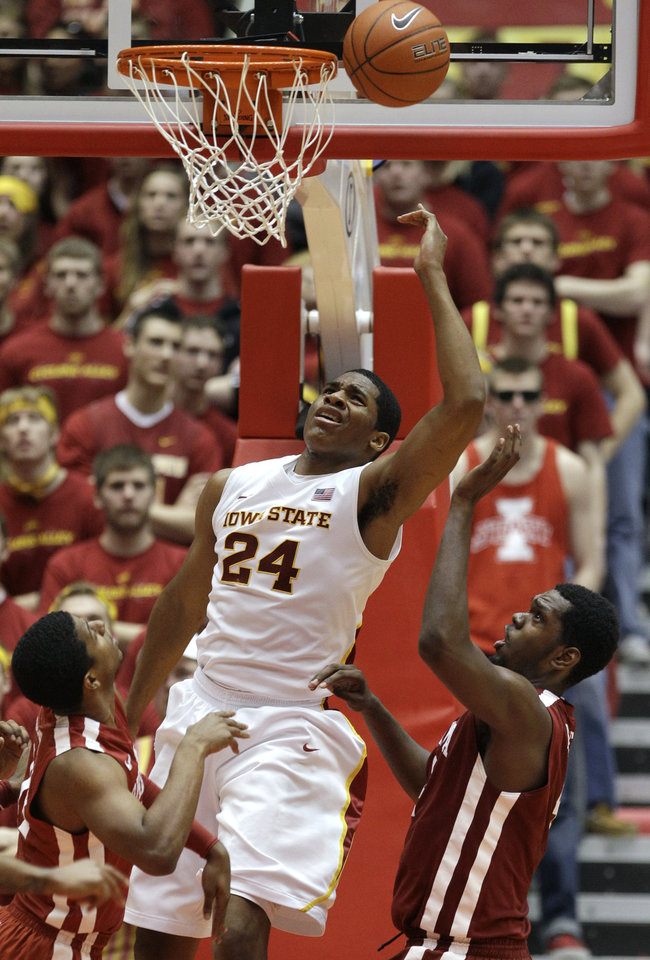 Iowa State center Percy Gibson (24) shoots over Oklahoma's Cameron Clark, left, and Andrew Fitzgerald, right, during the second half of an NCAA college basketball game, Saturday, Feb. 18, 2012, in Ames, Iowa.  Iowa State won 80-69. (AP Photo/Charlie Neibergall) ORG XMIT: IACN107