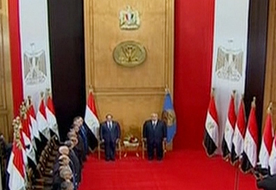 Photo - This image made from Egyptian State Television shows soon to be sworn in President Abdel-Fattah el-Sissi, left, and outgoing interim President Adly Mansour at the Supreme Constitutional Court in Cairo, Egypt, Sunday, June 8, 2014. El-Sissi's inauguration Sunday comes less than a year after the 59-year-old career infantry officer ousted the country's first freely elected president, the Islamist Mohammed Morsi, following days of mass protests by Egyptians demanding he step down. (AP Photo/Egyptian State Television)