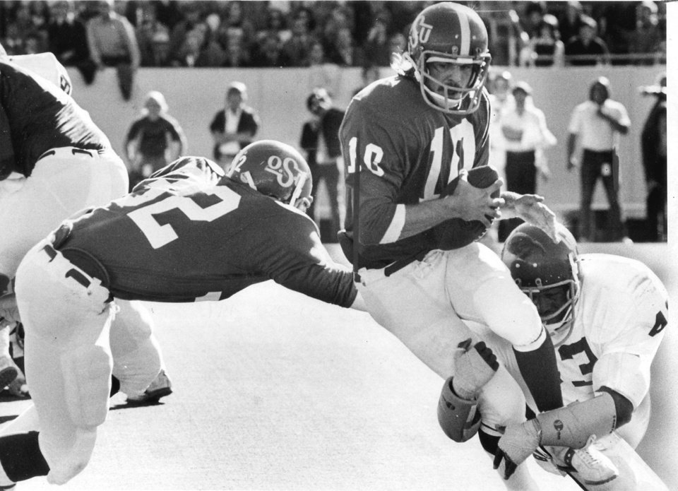 OSU quarterback Brent Blackman is tackled by OU defender Rod Shoate during the Bedlam college football game. The University of Oklahoma Sooners beat the Oklahoma State Cowboys 45-18 in Stillwater on Dec. 1, 1973. Staff photo