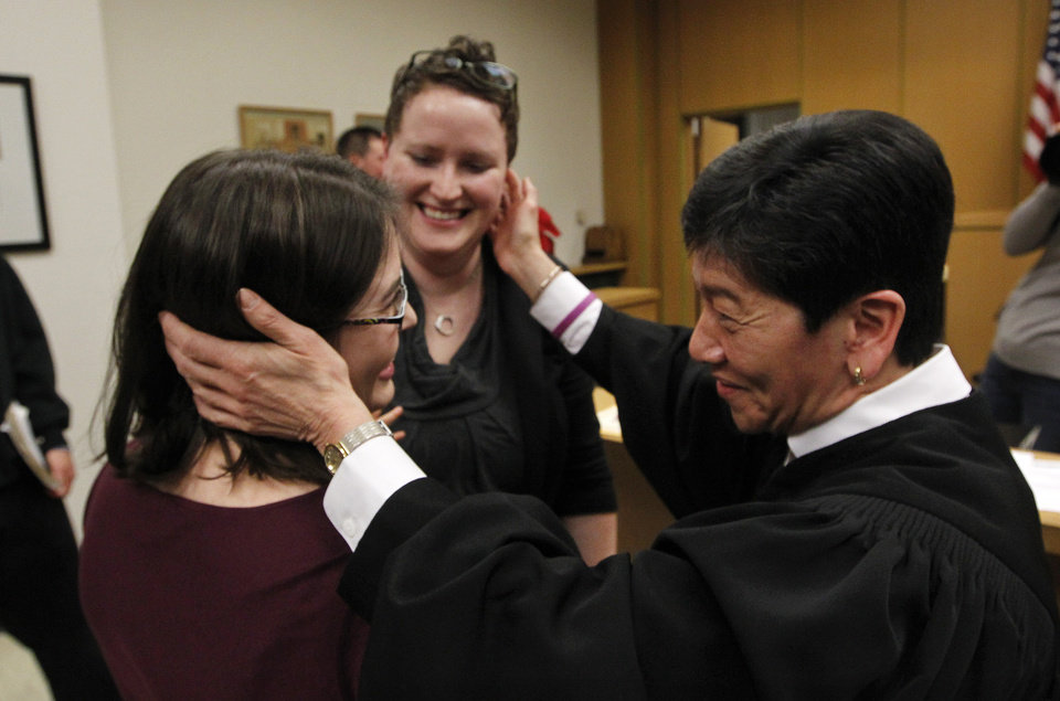 Photo - Judge Mary Yu, right, reaches to embrace Emily Cofer, left, and Sarah Cofer after declaring them wed moments after midnight in the in the King County Courthouse, becoming among the first gay couples to legally wed Sunday, Dec. 9, 2012, in Seattle. Gov. Chris Gregoire signed a voter-approved law legalizing gay marriage Wednesday, Dec. 5 and weddings for gay and lesbian couples began in Washington on Sunday, following the three-day waiting period after marriage licenses were issued earlier in the week. (AP Photo/Elaine Thompson)