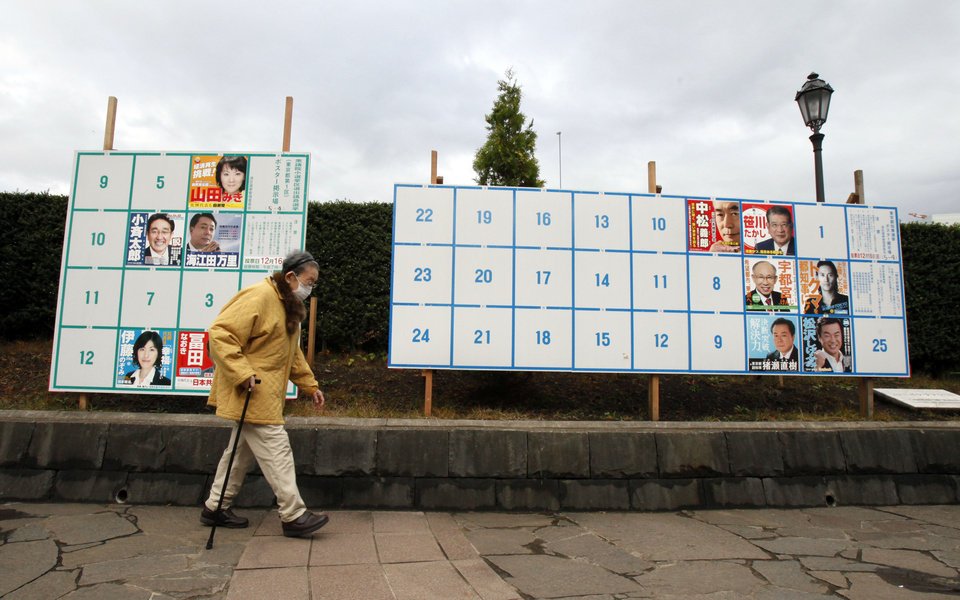 An elderly woman walks by candidates' poster boards for parliamentary elections, left, and Tokyo Gubernatorial election in Tokyo Tuesday, Dec. 4, 2012. Leaders for Japan's biggest political parties kicked off Tuesday the campaign for parliamentary elections to be held in less than two weeks with visits to nuclear crisis-hit Fukushima prefecture. (AP Photo/Koji Sasahara)