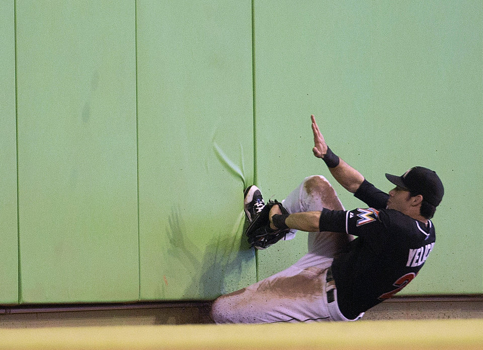 Photo - Miami Marlins outfielder Christian Yelich slides into the wall chasing a foul ball hit by Washington Nationals batter Bryce Harper during the seventh inning of a baseball game in Miami, Wednesday, July 30, 2014. The Nationals won 4-3. Yelich did not make the catch. (AP Photo/J Pat Carter)
