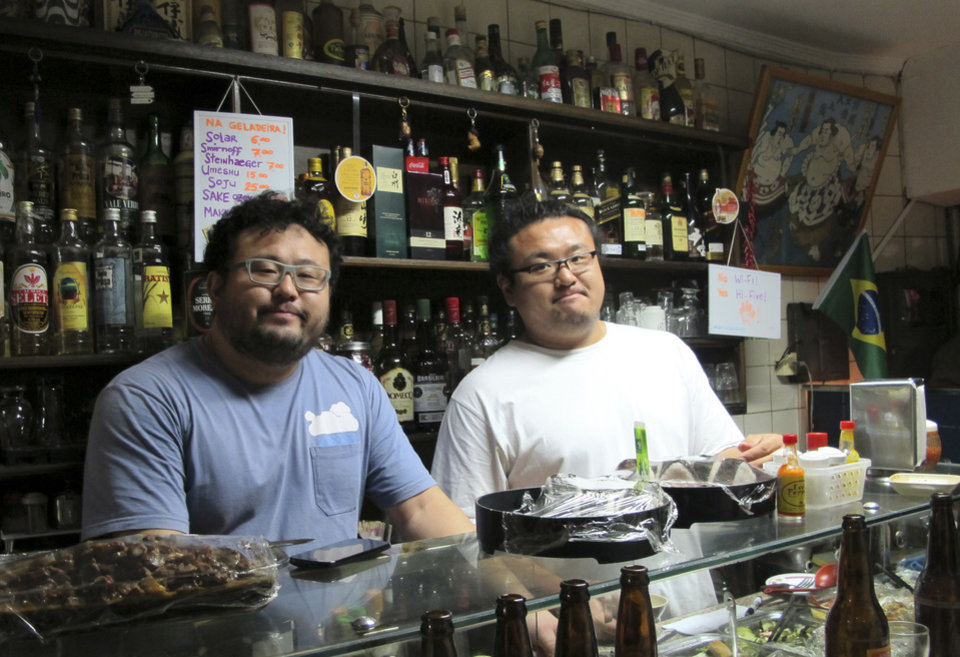 "Photo - In this June 10, 2014 photo,  William Takahiro Higuchi, left, and Wagner Yoshihiro Higuchi tend the Bar Kintaro, in Asian-flavored Libertade district of Sao Paulo, Brazil. Brazil hosts the world's largest ethnic Japanese population outside Japan -1.5 million, or half of the roughly 3 million scattered around the globe.  Many ""Nikkei"" like the Higuchi brothers have forged vibrant hybrid identities where sumo meets samba.  (AP Photo/Joji Sakurai)"