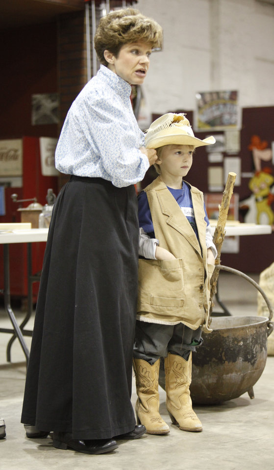 Five-year-old Nehemiah Steward wears cowboy clothing as the Edmond Historical Society's Christy Adel re-enacts the part of a school marm during a spring break class about life in the 1800s, at the Edmond Historical Society and Museum in Edmond, OK, Tuesday, March 20, 2012,  By Paul Hellstern, The Oklahoman