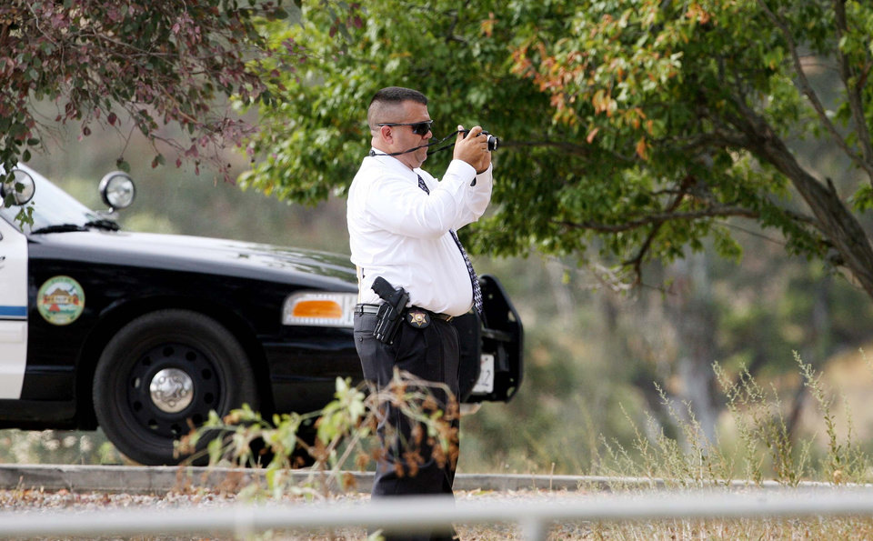 A sheriff's investigator takes photographs during the search for possible human remains found at the home of 11-year-old Terry Dewayne Smith Jr., who vanished over the weekend, in rural Menifee, Calif. Wednesday, July 10, 2013. Investigators served a search warrant before dawn at the home, Riverside County sheriff's Deputy Albert Martinez said, hours after they had told volunteers to stop searching the desert and brushlands of Menifee. (AP Photo/The Press-Enterprise, Frank Bellino)  NO SALES; MAGS OUT; MANDATORY CREDIT