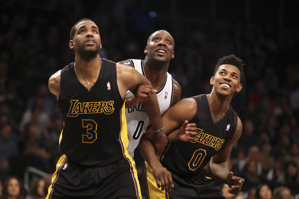 Photo - Brooklyn Nets center Andray Blatche, center, Los Angeles Lakers power forward Shawne Williams (3) and small forward Nick Young, right, look up for a rebound in the second quarter of an NBA basketball game at the Barclays Center, Wednesday, Nov. 27, 2013, in New York. (AP Photo/John Minchillo)