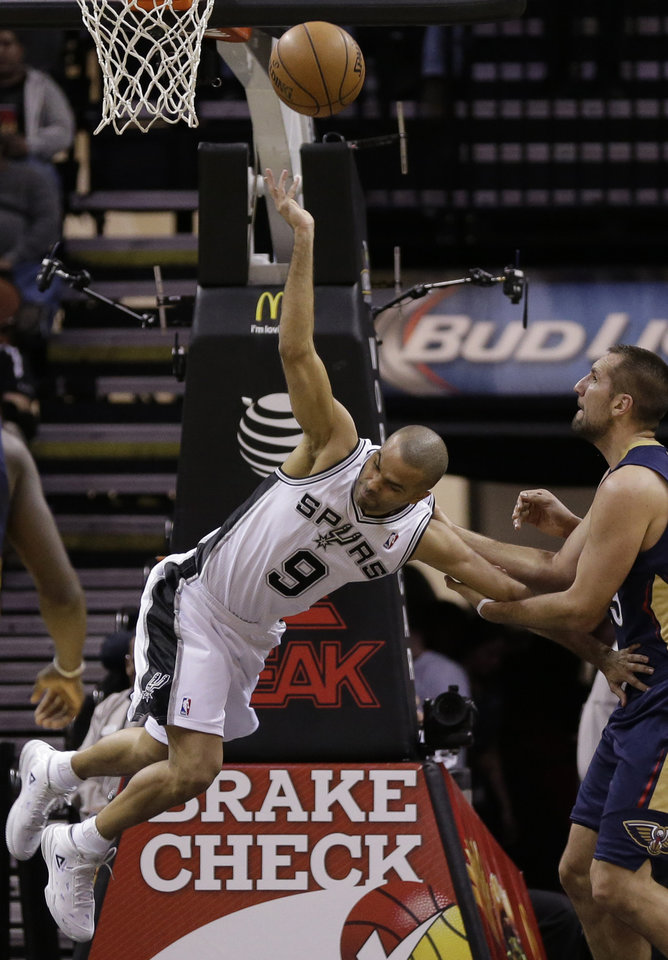Photo - New Orleans Pelicans' Ryan Anderson, right, grabs the arm of San Antonio Spurs' Tony Parker (9), of France, to keep him from scoring during the first half of an NBA basketball game, Monday, Nov. 25, 2013, in San Antonio. (AP Photo/Eric Gay)