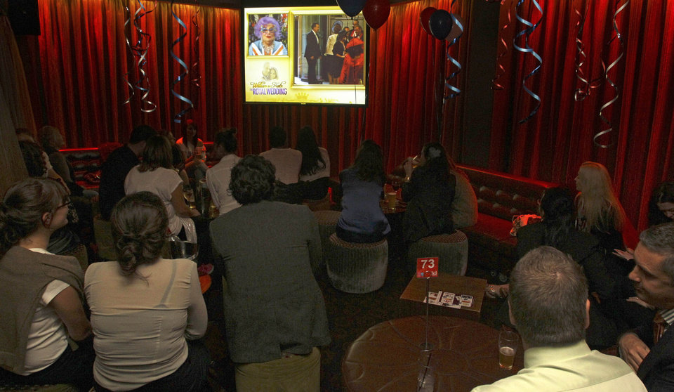 Photo - Patrons watch the Royal Wedding on TV during a party at the Ancient Britain (the AB) hotel in Sydney, Australia, Friday, April 29, 2011. The hotel is hosting the party during celebrations for the wedding of Prince William and Kate Middleton. (AP Photo/Rob Griffith) ORG XMIT: SYD111