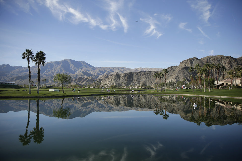 Photo - The group following Trevor Immelman and Jason Bohnon are reflected in the pond between the first and 10th hole during the third round of the Humana Challenge golf tournament on the Palmer Private course at PGA West Saturday, Jan. 18, 2014, in La Quinta, Calif. (AP Photo/Chris Carlson)