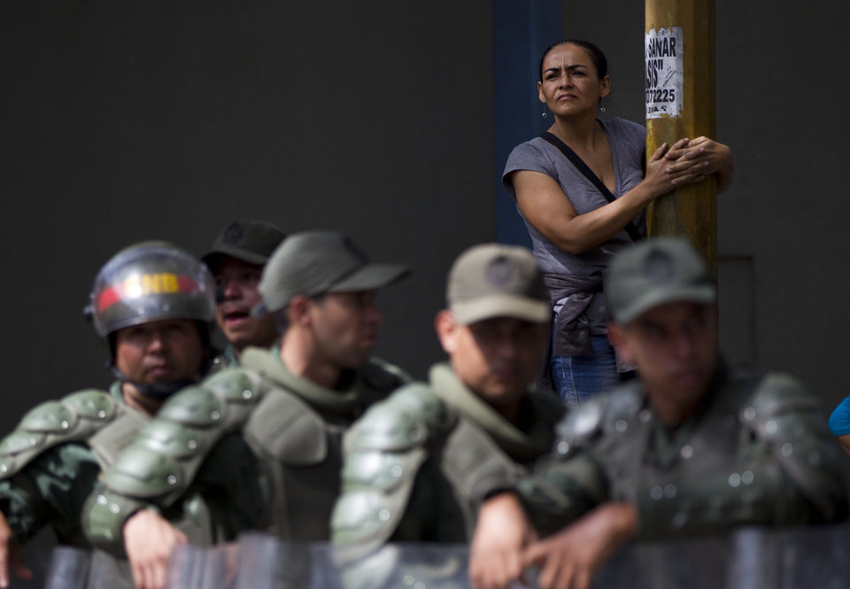 Photo -   An inmate's relative stands behind National Guard soldiers outside La Planta prison in Caracas, Venezuela, Saturday, April 28, 2012. Hundreds of inmate's relatives were not allowed to enter for normal visiting hours because they were canceled after authorities foiled plans for a prison break on Friday. Venezuelan authorities say they discovered a tunnel that inmates had dug leading to a sewer. (AP Photo/Ariana Cubillos)