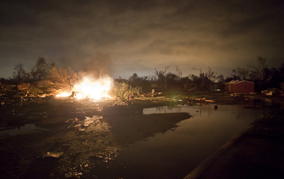 Photo -   A fire burns in the Pinaire mobile home park in Wichita, Kansas after a tornado caused massive destruction in the area on Saturday night April 14, 2012. Tornadoes were spotted across the Midwest and Plains on Saturday as an outbreak of unusually strong weather seized the region, and forecasters sternly warned that