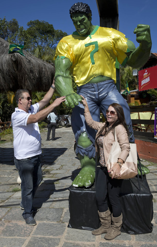 Photo - Soccer fans pose for pictures with a statue of super hero Hulk near the Granja Comary training center, where Brazil is training during the World Cup, in Teresopolis, Brazil, Wednesday, June 25, 2014. The statue is in tribute to Brazil's soccer player named Hulk. (AP Photo/Andre Penner)