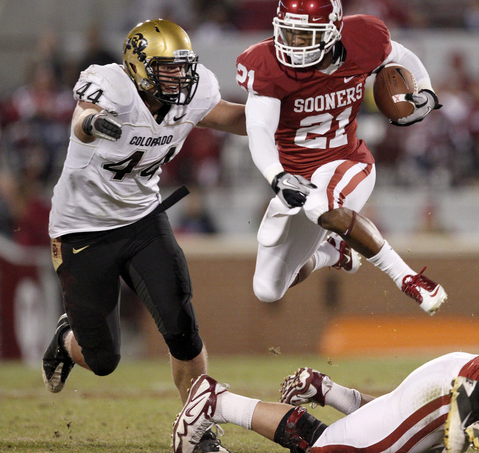 Photo - OU's Brennan Clay leaps in front of Colorado's Harold Mobley during the college football game between the University of Oklahoma (OU) Sooners and the University of Colorado Buffaloes at Gaylord Family-Oklahoma Memorial Stadium in Norman, Okla., Saturday, October 30, 2010. Photo by Bryan Terry, The Oklahoman