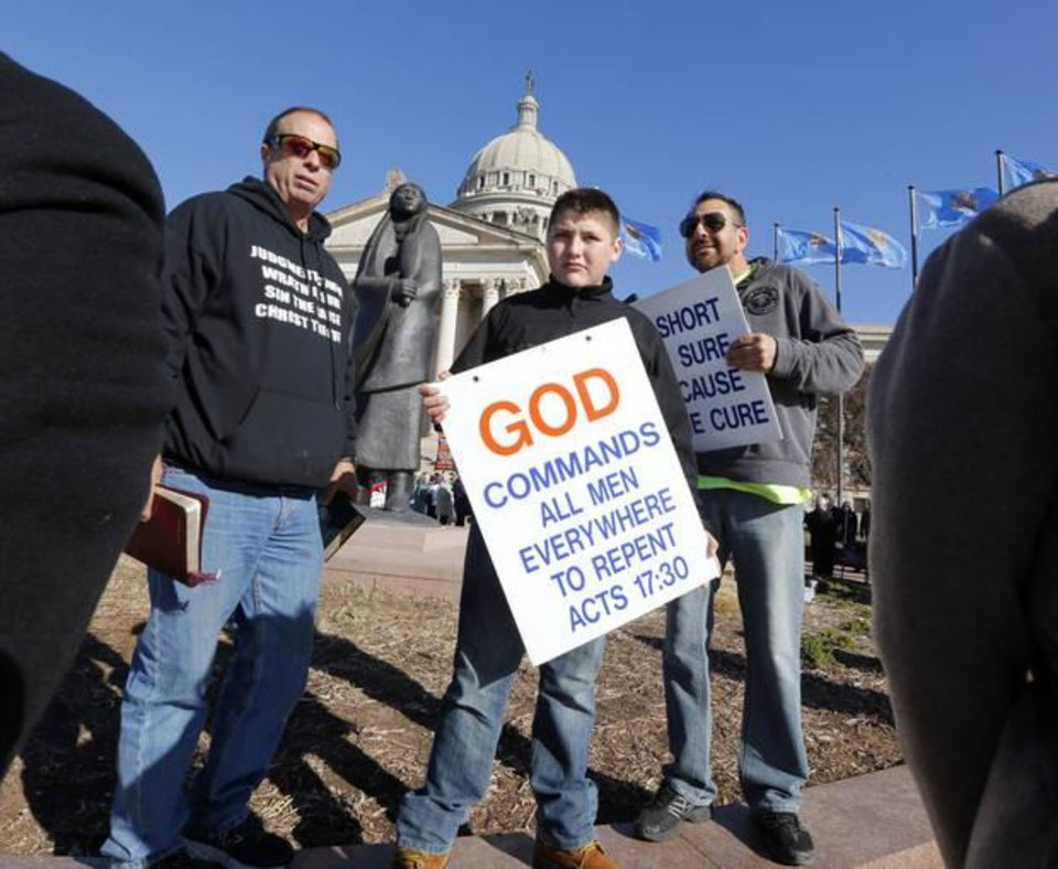"Photo - David Grisham, pastor of ""Repent"" in Amarillo, Anthony Rios and Justin Schoelen, both from Kingfisher, hold signs and making anti-Islamic statements as Oklahoma Muslims enter the State Capitol building to attend ""Muslim Day at the Capitol"" on Friday, Feb. 26, 2016 in Oklahoma City, Okla.  Photo by Steve Sisney, The Oklahoman"