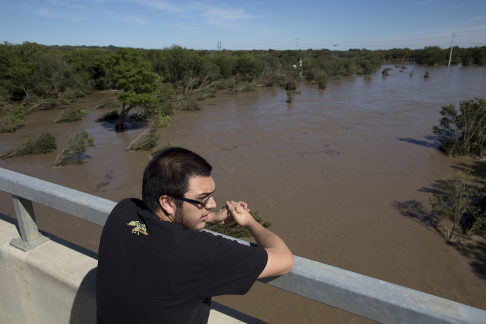 Photo - Jake Navarro looks out over a flooded Onion Creek on Thursday Oct. 31, 2013 in Austin, Texas.  The National Weather Service said more than a foot of rain fell in Central Texas, including up to 14 inches in Wimberley, since rainstorms began Wednesday. (AP Photo/ Tamir Kalifa)