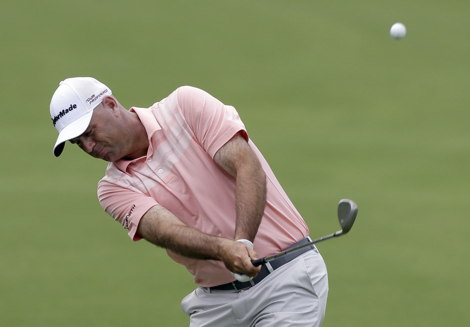 Photo - Stewart Cink hits his approach shot on the 18th hole during the first round of the Wells Fargo Championship golf tournament in Charlotte, N.C., Thursday, May 1, 2014. (AP Photo/Bob Leverone)