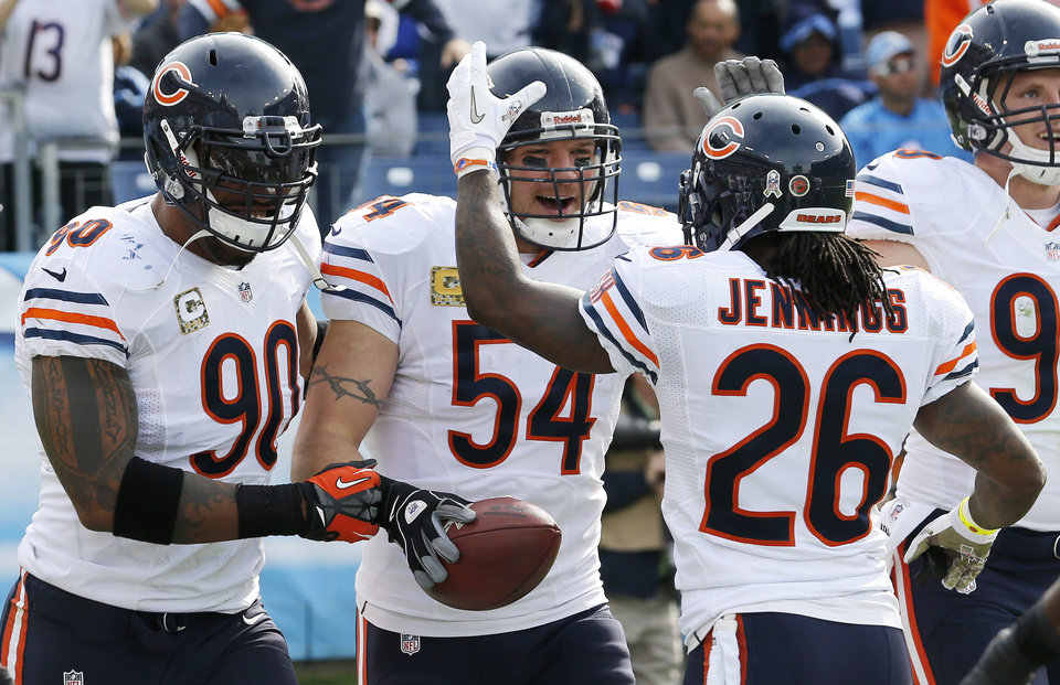 Photo -   Chicago Bears middle linebacker Brian Urlacher (54) celebrates with Julius Peppers (90) and Tim Jennings (26) after Urlacher returned an interception for a touchdown against the Tennessee Titans in the first quarter of an NFL football game on Sunday, Nov. 4, 2012, in Nashville, Tenn. (AP Photo/Joe Howell)