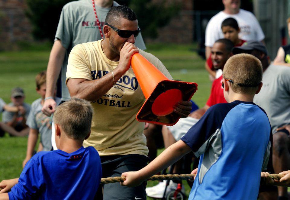Photo - University of Oklahoma's (OU) co-offensive coordinator Jay Norvell's brother Aaron Norvell gets involved with Tug of War Tuesday during Jay's annual youth camp at Whittier Middle School on Tuesday, June 17, 2014 in Norman, Okla.  Photo by Steve Sisney, The Oklahoman