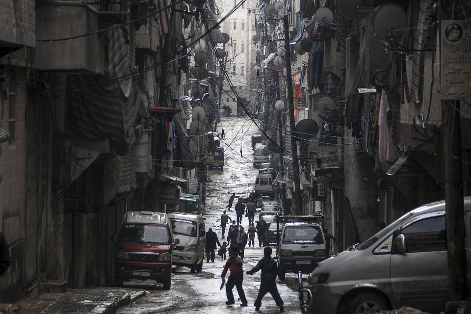 Syrians walk past damaged homes during heavy fighting between Free Syrian Army fighters and government forces in Aleppo, Syria, Tuesday, Dec. 4, 2012. (AP Photo/Narciso Contreras)