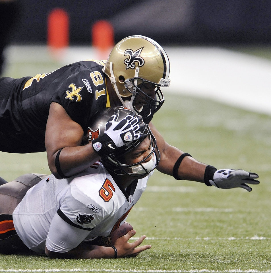 FILE - This Dec. 27, 2009 file photo shows New Orleans Saints defensive end Will Smith (91) grabbing Tampa Bay Buccaneers quarterback Josh Freeman (5) for a sack in the first half of an NFL football game in New Orleans. Smith is one of four players punished for participating in a pay-for-pain bounty system. NFL Commissioner Roger Goodell's ruling was announced Wednesday, May 2, 2012. (AP Photo/Bill Feig, File)