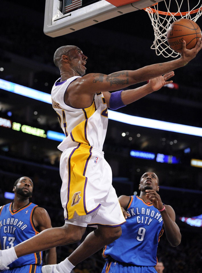 Photo - L.A. LAKERS: Los Angeles Lakers guard Kobe Bryant, center, puts up a shot as Oklahoma City Thunder guard James Harden, left, and center Serge Ibaka defend during the first half of their NBA basketball game, Sunday, Nov. 22, 2009, in Los Angeles.  (AP Photo/Mark J. Terrill) ORG XMIT: LAS102