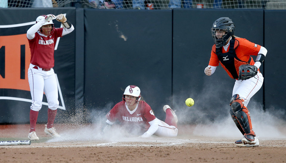 Photo -  Oklahoma's Nicole Mendes (11) as slides home and Kelsey Arnold celebrates as Oklahoma State's Mackenzie Thomas tries to catch the ball in the fifth inning of the bedlam softball game between OSU and OU in Stillwater on Wednesday. [PHOTO BY BRYAN TERRY, THE OKLAHOMAN]