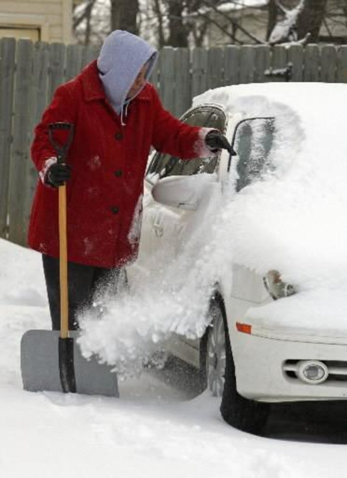 Photo - Trisha Ryan brushes snow from her car and cleans with a shovel as the second round of show in a week moved into the area on Wednesday, February 9, 2011, in Norman, Okla. Photo by Steve Sisney