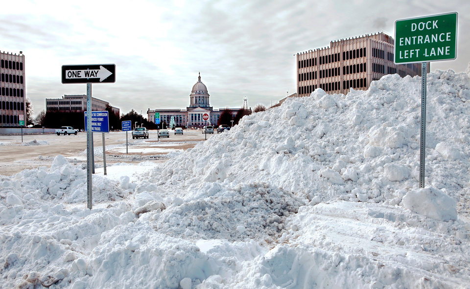 Photo - Large piles of snow remain after trucks cleared snow from the parking lots of state office buildings north of the state Capitol Thursday, Feb. 3, 2011. Photo by Jim Beckel, The Oklahoman