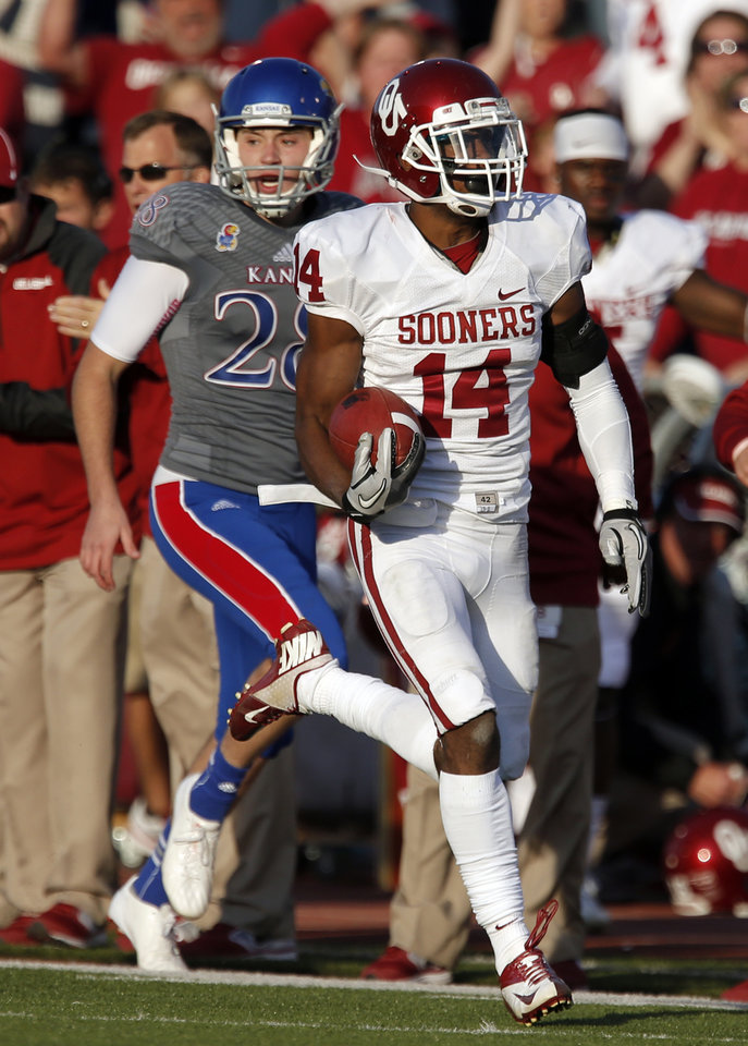 OU's Aaron Colvin (14) returns a blocked extra point kick for a safety as KU's Matthew Wyman (28) tries to chase him down in the fourth quarter during of the college football game between the University of Oklahoma Sooners (OU) and the University of Kansas Jayhawks (KU) at Memorial Stadium in Lawrence, Kan., Saturday, Oct. 19, 2013. OU won 34-19. Photo by Sarah Phipps, The Oklahoman