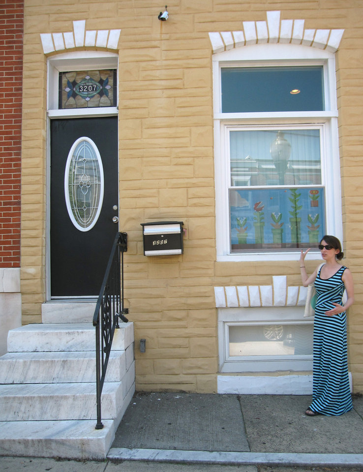 Photo - This June 8, 2014 photo shows Amanda Smit-Peters showing an example of painted window screens in the Highlandtown neighborhood of Baltimore. Smit-Peters, Main Street manager for the neighborhood, is working with local artists to bring back the urban folk art of painted screens. They were popular in the 20th century as a way to keep people walking by on the street from seeing inside Baltimore's row house windows. (AP Photo/Beth J. Harpaz)