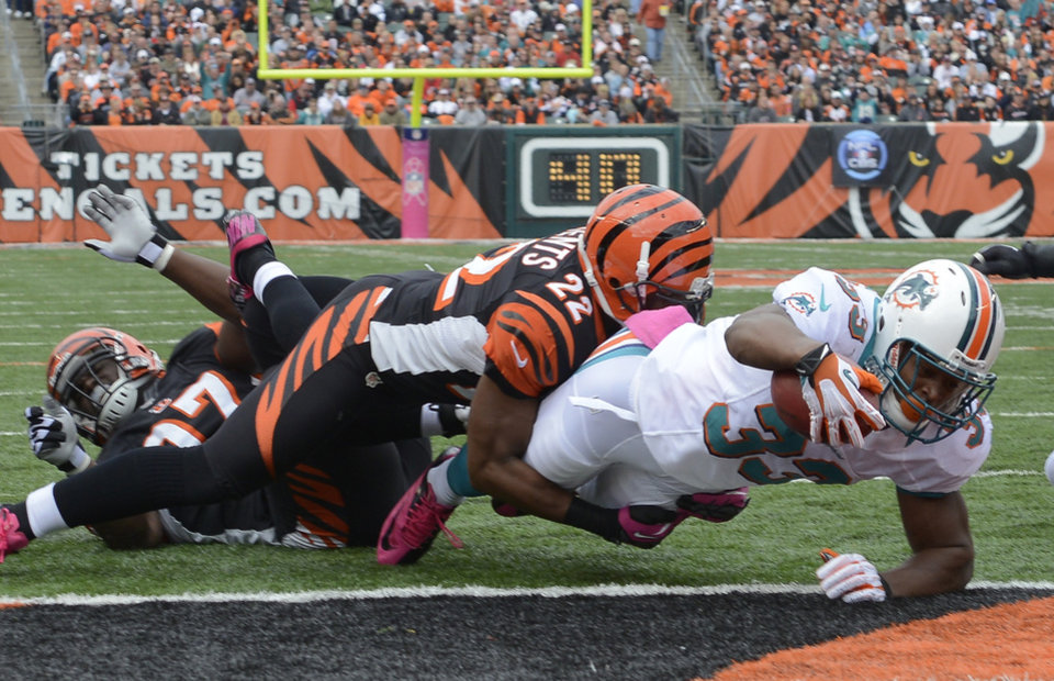 Miami Dolphins running back Daniel Thomas (33) dives past Cincinnati Bengals cornerback Nate Clements (22) for a one-yard touchdown run in the first half of an NFL football game, Sunday, Oct. 7, 2012, in Cincinnati. (AP Photo/Michael Keating)