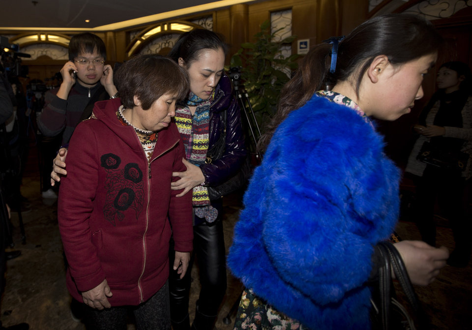 Photo - Chinese relatives of passengers aboard a missing Malaysia Airlines plane leave a hotel room after meeting with Malaysian officials, in Beijing, China Wednesday, March 12, 2014. The missing Malaysian jetliner may have attempted to turn back before it vanished from radar, but there is no evidence it reached the Strait of Malacca, Malaysia's air force chief said Wednesday, denying reported remarks he said otherwise. The statement suggested continued confusion over where the Boeing 777 might have ended up, more than four days after it disappeared en route to Beijing from Kuala Lumpur with 239 people on board. (AP Photo/Andy Wong)