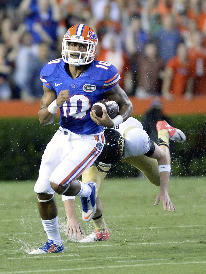 Photo - Florida's Valdez Showers (10) runs back a 66-yard kickoff return past Idaho defensive lineman Anthony Rice during the first half of an NCAA college football game in Gainesville, Fla., Saturday, Aug. 30, 2014. (AP Photo/Phil Sandlin)