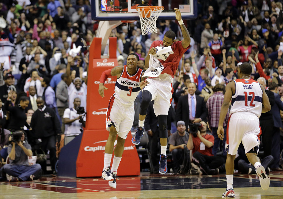 Washington Wizards guard Bradley Beal (3) and forward Trevor Ariza, center, celebrate Beal\'s game winning shot in the second half of an NBA basketball game against the Oklahoma City Thunder Monday, Jan. 7, 2013, in Washington. The Wizards won 101-99.(AP Photo/Alex Brandon) ORG XMIT: VZN108
