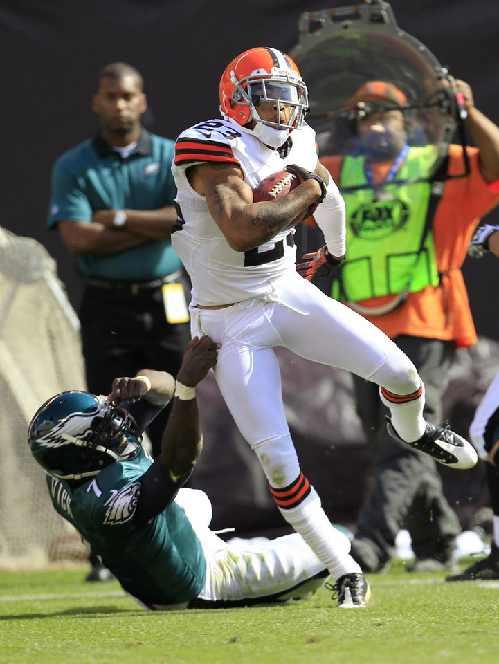 Photo -   Cleveland Browns defensive back Joe Haden (23) is tackled by Philadelphia Eagles quarterback Michael Vick (7) after intercepting the ball in the third quarter of an NFL football game on Sunday, Sept. 9, 2012, in Cleveland. (AP Photo/Tony Dejak)