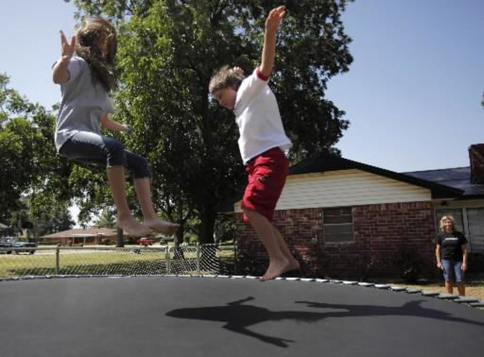 Photo - Hayden and Taylor Harjo, both 11, jump on their trampoline in Seminole, Okla., July 4, 2012. Photo by Garett Fisbeck, The Oklahoman