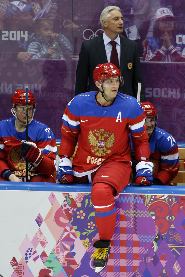 Photo - Russia forward Alexander Ovechkin watches play against Slovenia from the bench in the second period of a men's ice hockey game at the 2014 Winter Olympics, Thursday, Feb. 13, 2014, in Sochi, Russia. (AP Photo/Mark Humphrey)