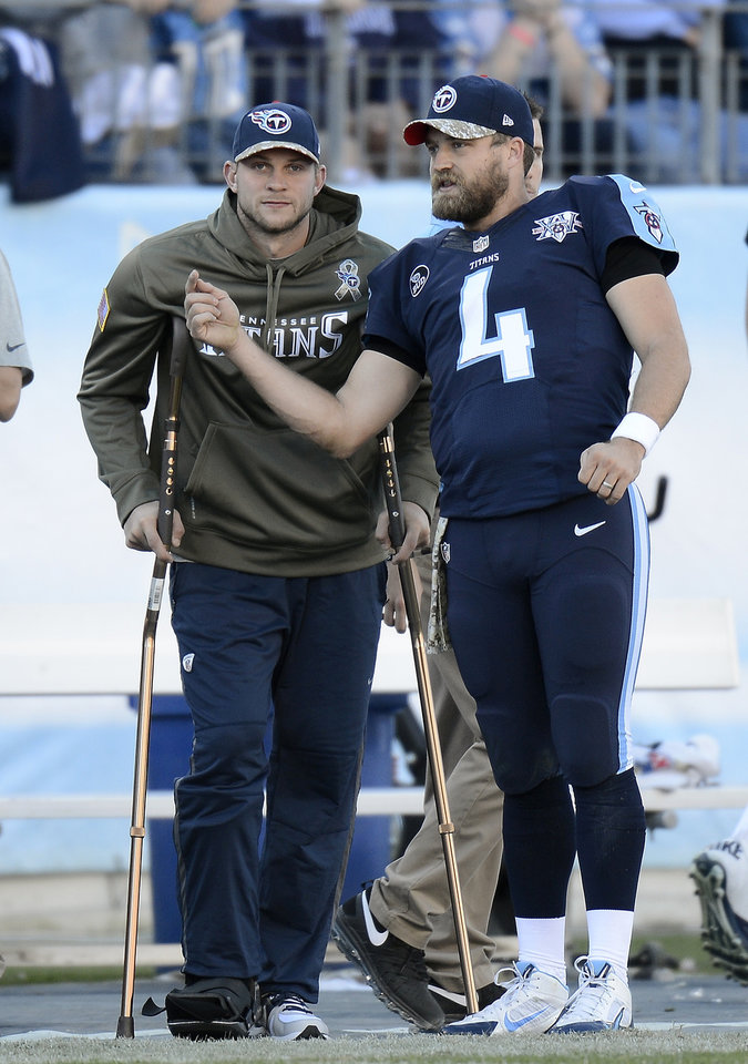 Photo - Tennessee Titans quarterback Jake Locker, left, watches from the sideline as he talks with fellow quarterback Ryan Fitzpatrick (4) in the fourth quarter of an NFL football game on Sunday, Nov. 10, 2013, in Nashville, Tenn. Locker injured his foot earlier in the game. (AP Photo/Mark Zaleski)
