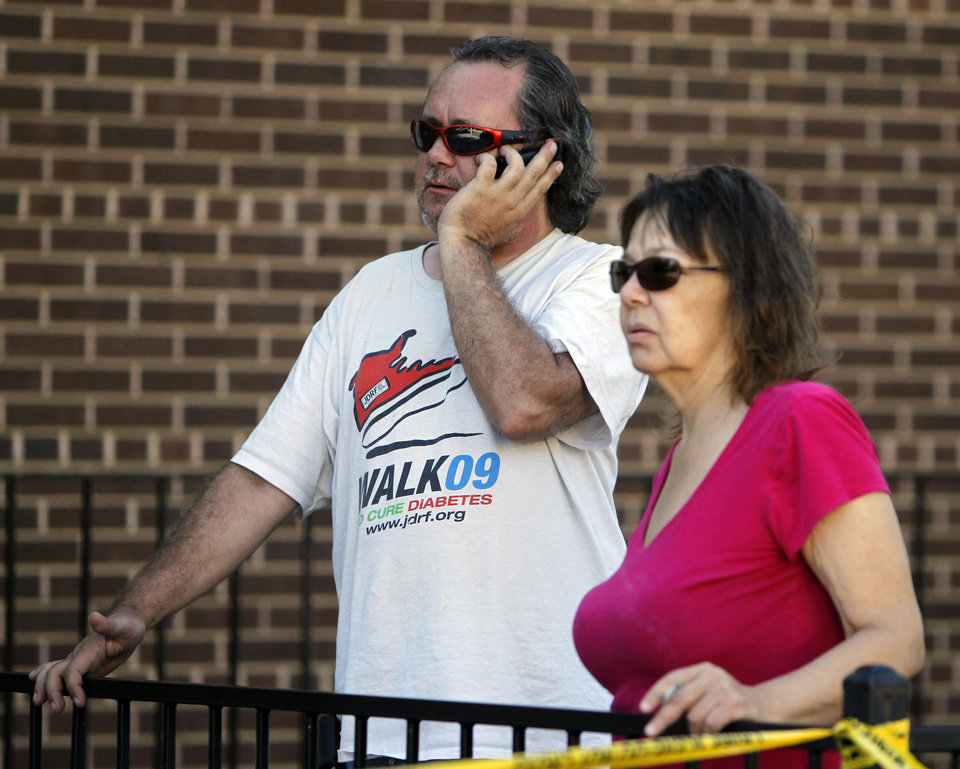 Photo - John Priest, left, and Vory Boots watch the police action at an apartment where the suspect in a theatre shooting lived in Aurora, Colo., on Friday, July 20, 2012. The couple were evacuated from their apartment across from the suspects.  As many as 12 people were killed and 50 injured at a shooting at the Century 16 movie theatre on Friday. The suspect is identified as 24-year-old James Holmes.  (AP Photo/Ed Andrieski) ORG XMIT: COEA120