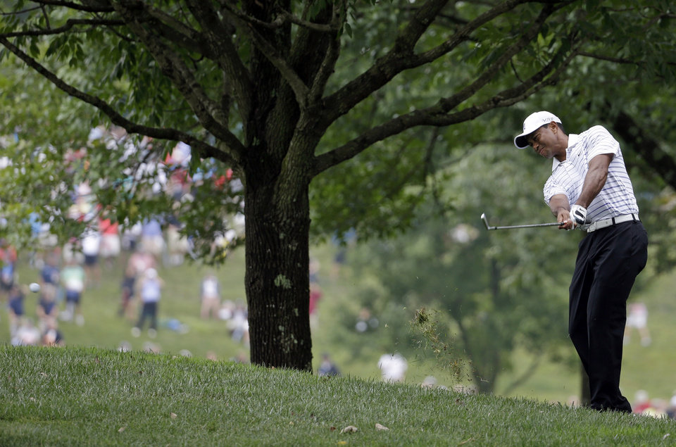 Photo - Tiger Woods hits from rough on the first hole during the second round of the PGA Championship golf tournament at Valhalla Golf Club on Friday, Aug. 8, 2014, in Louisville, Ky. (AP Photo/Jeff Roberson)