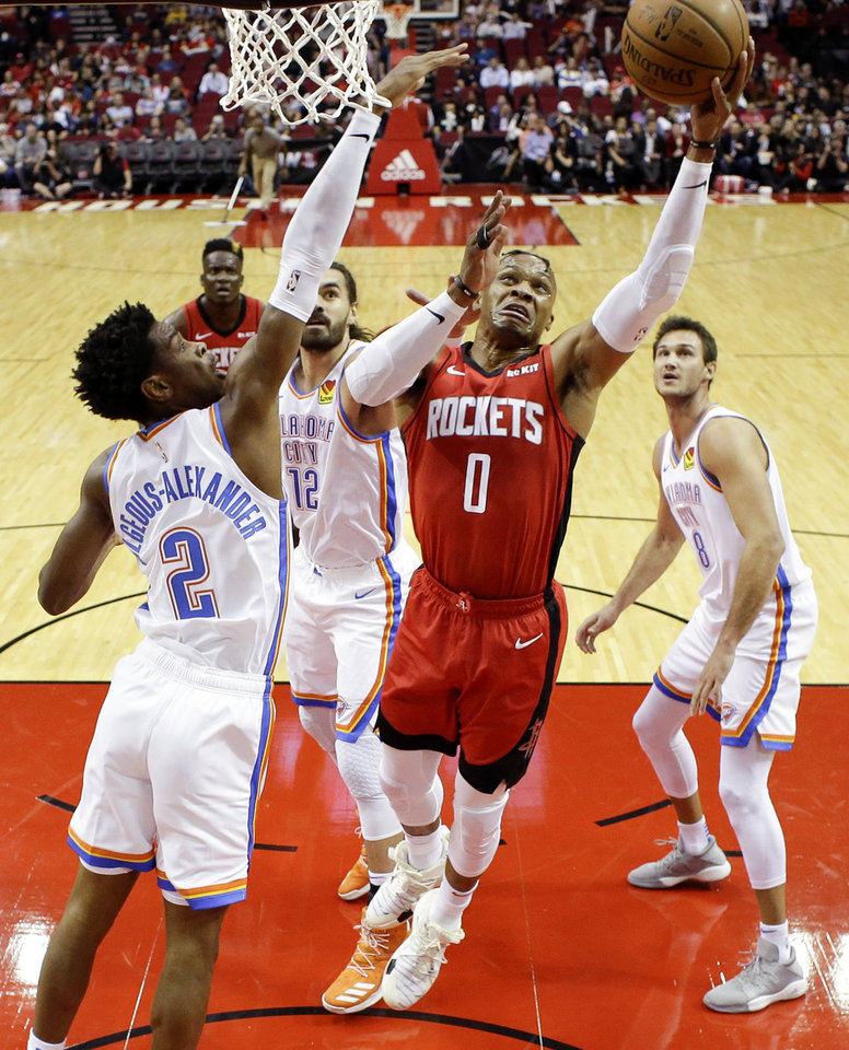 Photo - Houston Rockets guard Russell Westbrook (0) drives to the basket as Oklahoma City Thunder guard Shai Gilgeous-Alexander (2) defends during the first half of an NBA basketball game, Monday, Oct. 28, 2019, in Houston. (AP Photo/Eric Christian Smith)