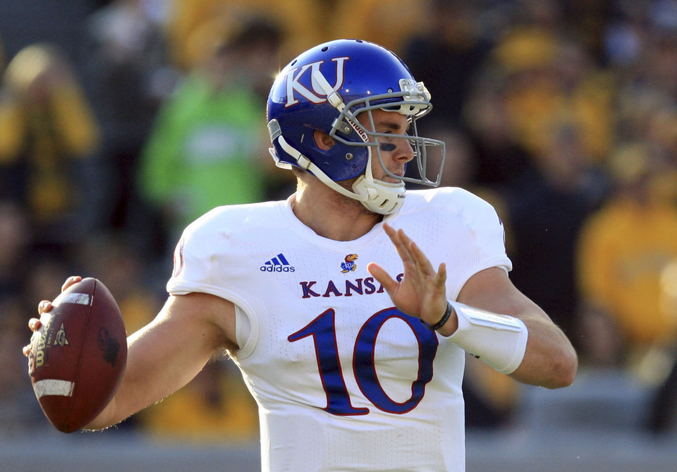 Photo - Kansas quarterback Dayne Crist (10) looks to pass during the first quarter of their NCAA college football game against West Virginia in Morgantown, W.Va., on Saturday, Dec. 1, 2012. West Virginia won 59-10.  (AP Photo/Christopher Jackson)