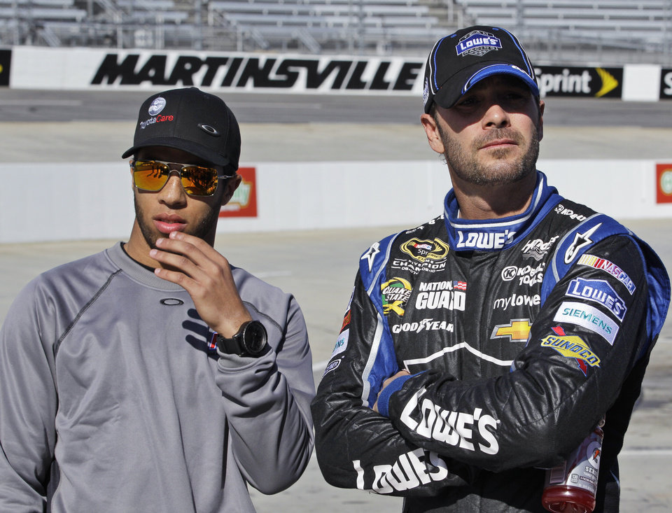 Jimmie Johnson, right, watches NASCAR Sprint Cup qualifying with driver Darrell Wallace Jr. at Martinsville Speedway in Martinsville, Va., Friday, April 5, 2013. Johnson won the pole for Sunday's race. (AP Photo/Steve Helber)