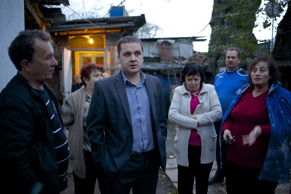 Photo - In this photo taken on Wednesday, Nov. 27, 2013, Igor Zarytovsky, center, and his father Vladimir, left, gather with their neighbors in the yard of the railroad house in the village of Vesyoloye outside Sochi, Russia. As the Winter Games are getting closer, many Sochi residents are complaining that their living conditions only got worse and that authorities are deaf to their grievances. (AP Photo/Alexander Zemlianichenko)
