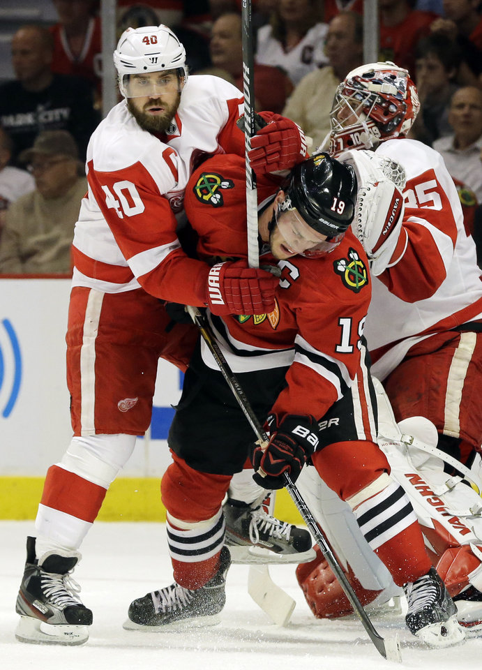Photo - Chicago Blackhawks' Jonathan Toews (19) battles for position in front of the goal with Detroit Red Wings' Henrik Zetterberg (40) during the second period of Game 2 of the NHL hockey Stanley Cup playoffs Western Conference semifinals in Chicago, Saturday, May 18, 2013. (AP Photo/Nam Y. Huh)
